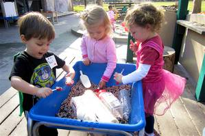 Children playing with spoons and containers in a tub of beans