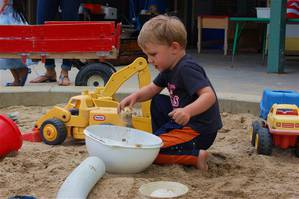 Boy playing in the sandbox with colander