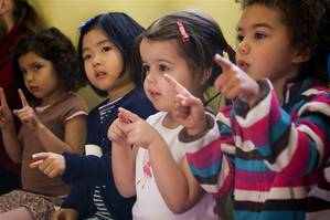 Children following along with the teacher during circle time