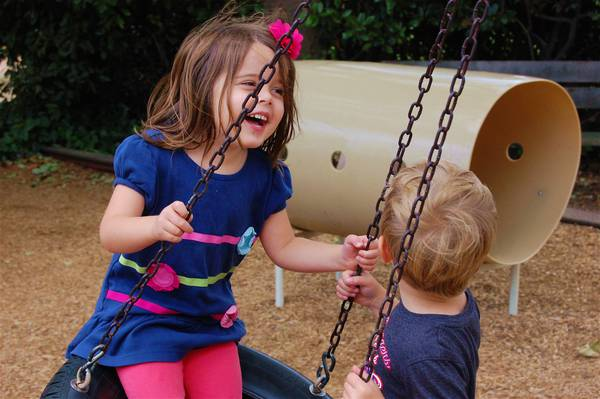 Two children laughing on the tire swing