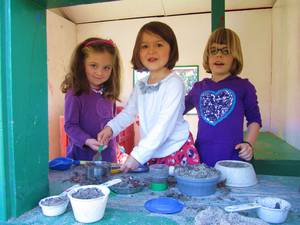 Three girls playing with sand and bowls outdoors